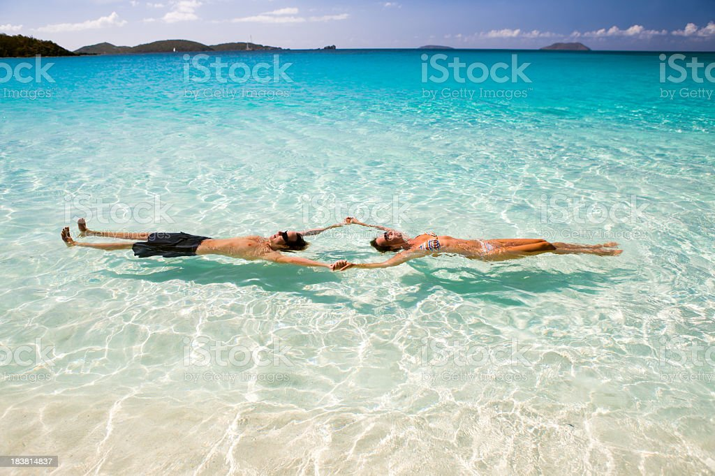 Honeymoon Couple Holding Hands And Floating At The Caribbean Stock