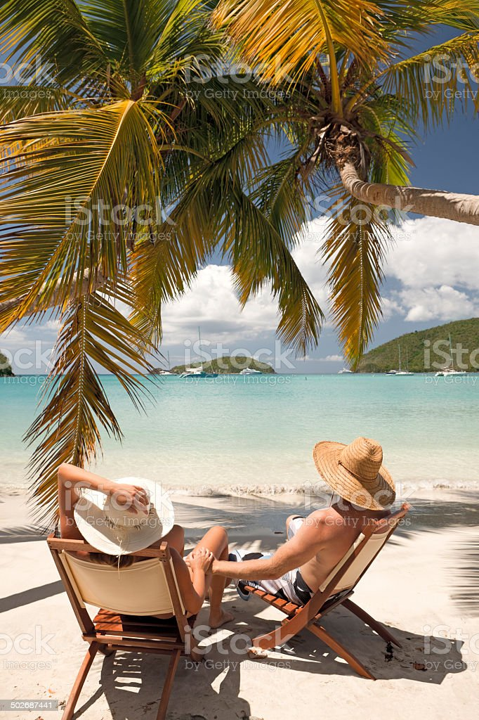 honeymoon couple holding hands and relaxing at a Caribbean beach stock photo