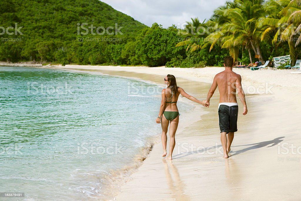 honeymoon couple holding hands and walking along a Caribbean beach stock photo