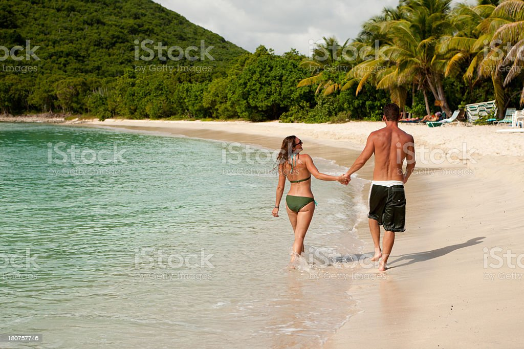 honeymoon couple holding hands and walking along a tropical beach royalty-free stock photo