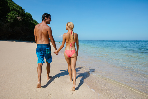 Honeymoon couple holding hands walking on beach