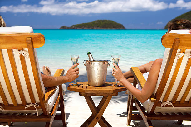 honeymoon couple in recliners drinking champagne at a caribbean beach - caribbean stock pictures, royalty-free photos & images
