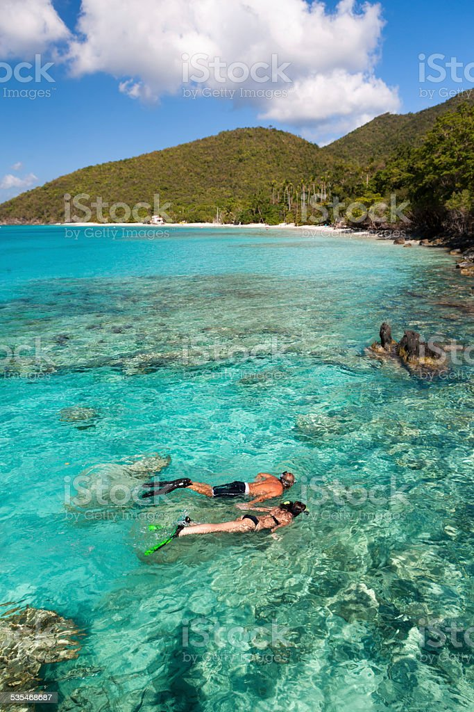 honeymoon couple snorkeling in the Caribbean crystal clear waters stock photo