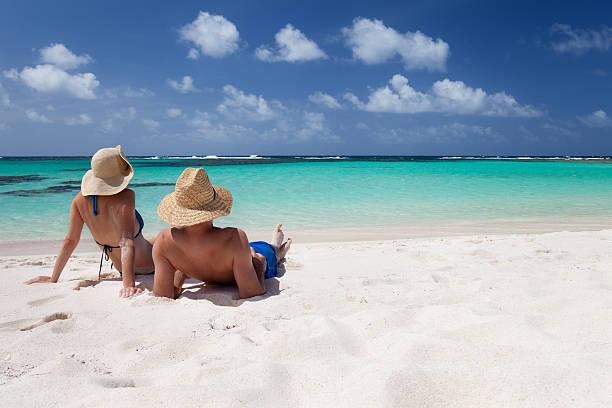 honeymoon  couple sunbathing on a beach in the Caribbean