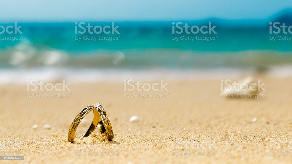 Honeymoon on tropical island, two wedding rings on the beach stock photo