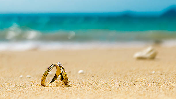 honeymoon on tropical island, two wedding rings on the beach - hochzeitsreise ohne mann stock-fotos und bilder