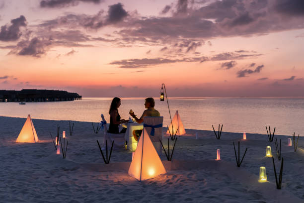 Honeymoon travel concept on a tropical beach Couple is having a private event dinner on a tropical beach during sunset time: Honeymoon travel concept romance stock pictures, royalty-free photos & images