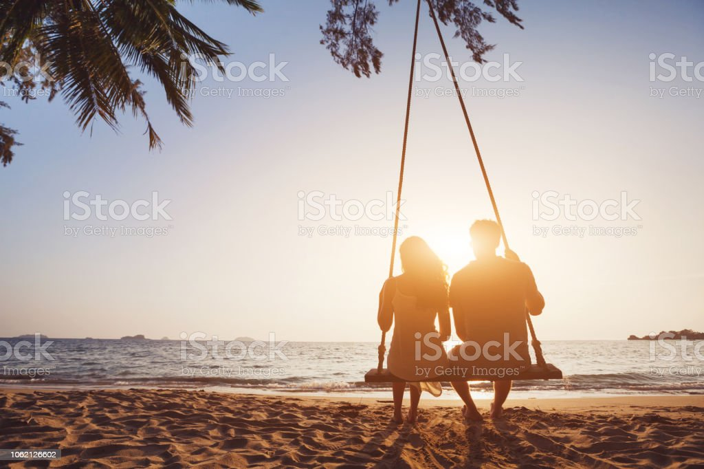 Honeymoon travel, silhouete of couple in love on the beach. romantic couple in love sitting together on rope swing at sunset beach, silhouettes of young man and woman on holidays or honeymoon Adult Stock Photo