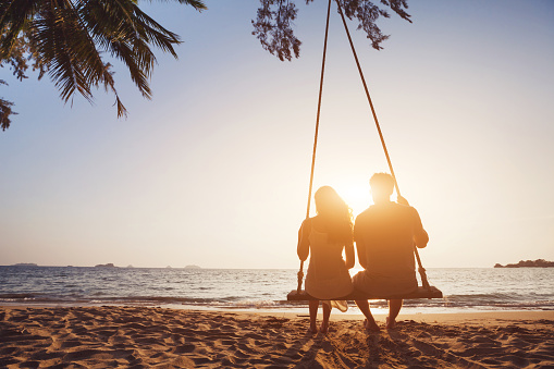 Honeymoon travel, silhouete of couple in love on the beach.