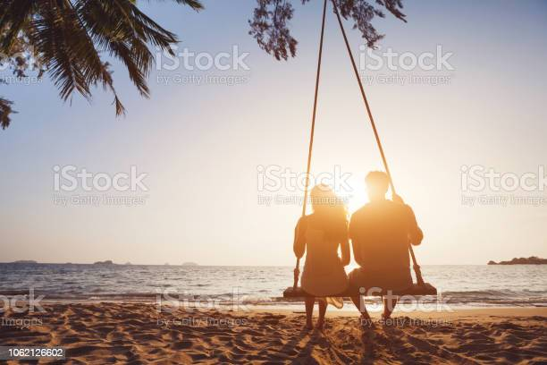 Photo of Honeymoon travel, silhouete of couple in love on the beach.