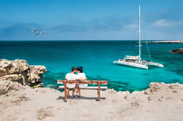 flitterwochen-reiseleiter hugging auf einer holzbank und genießt ihren tropischen urlaub. hochzeitsreise. junges, glückliches paar, das sich am strand zurücksitzt. blick auf ein verliebtes ehepaar im urlaub. reisende - hochzeitsreise zypern stock-fotos und bilder