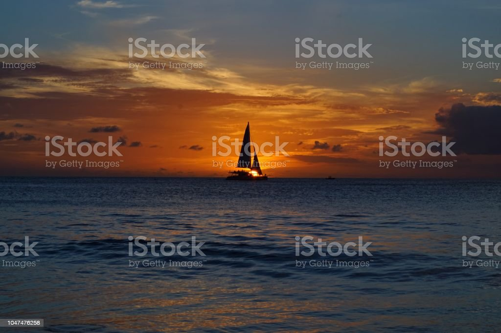 Honeymoon yacht through sunset in Barbados Caribbean stock photo