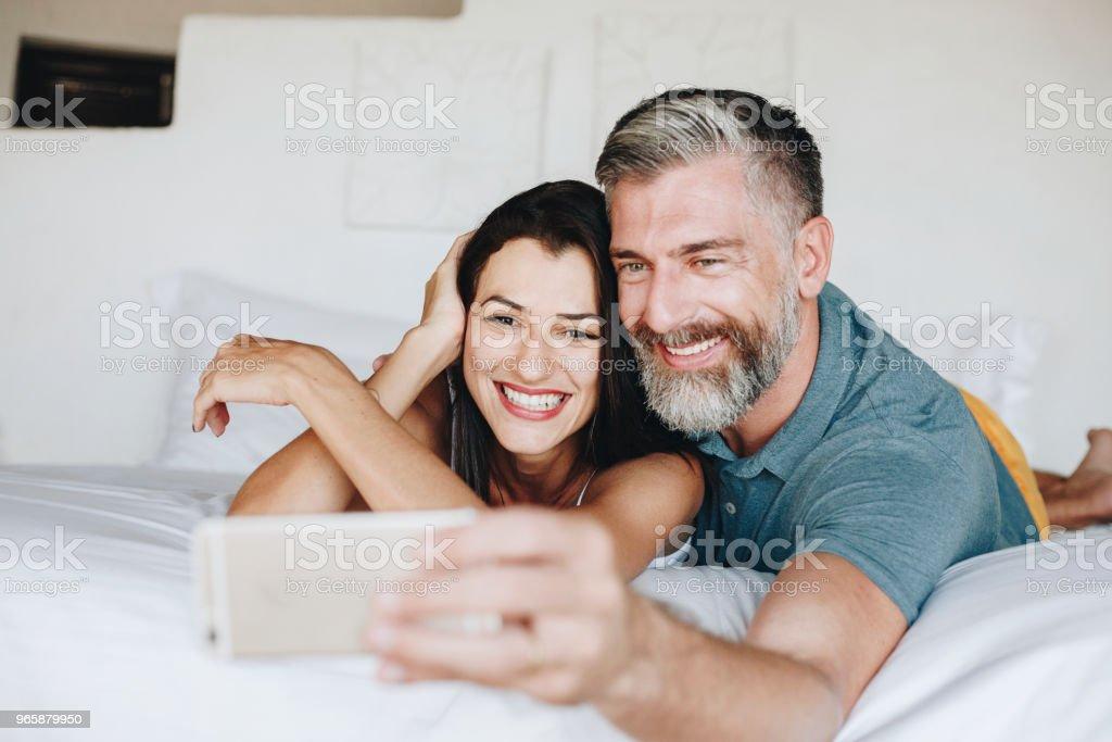 Honeymooners taking a selfie in bed - Royalty-free Adult Stock Photo