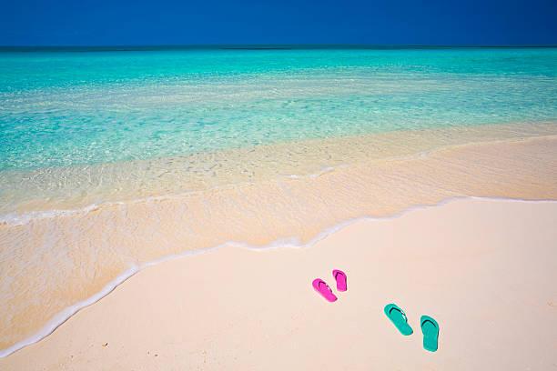 honeymooners'sandalen am unberührten weißen sandstrand - flitterwochen flip flops stock-fotos und bilder