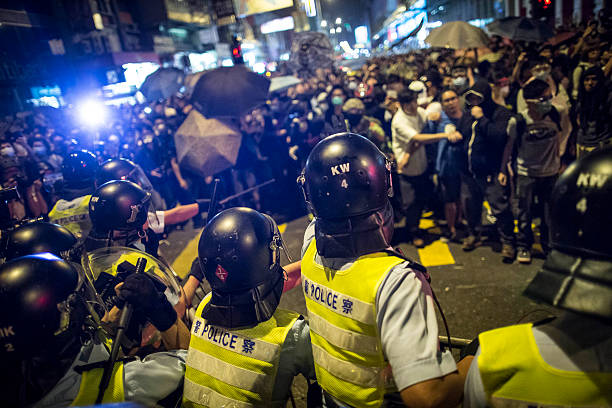 Hong Kong Democracy Protest Hong Kong, China - October 19, 2014: Riot police disperse protesters with baton at the occupied area in Mongkok district. riot police stock pictures, royalty-free photos & images