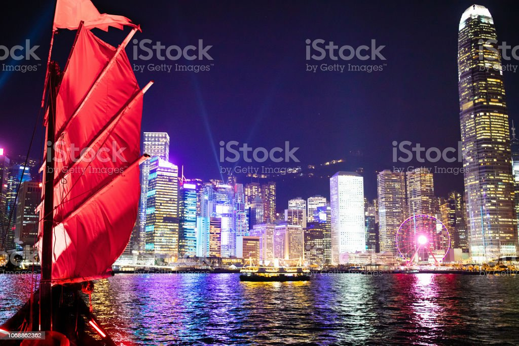 Hong Kong harbor view from junk boat at night Hong Kong harbor view from traditional junk boat at night during famous laser show. Travel in China, Asia. Sailing on historical ship in Hong Kong Victoria harbor at symphony of light evening show. Asia Stock Photo