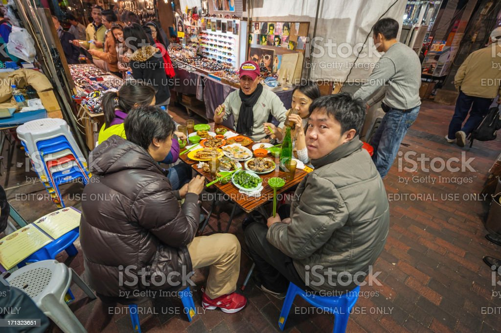 Hong Kong local diners at night market street cafe royalty-free stock photo