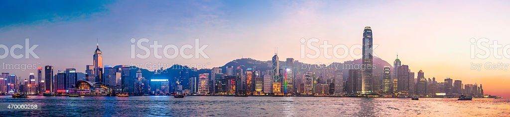 Hong Kong neon sunset iconic harbour skyscrapers illuminated panorama China Neon signs glowing on the iconic downtown skyline of Hong Kong Island at sunset, from the soaring spire of 2IFC past the Star Ferry Terminal and the financial hub of Exchange Square in the Central District to the New Bank of China and Wan Chai overlooking the tranquil waters of Victoria Harbour, China. ProPhoto RGB profile for maximum color fidelity and gamut. 2015 Stock Photo