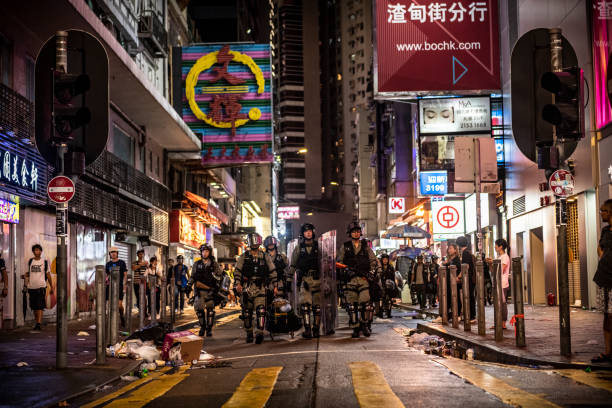 Hong Kong riot police in Causeway Bay Hong Kong riot police walk together down a road near Causeway Bay MTR station on Hong Kong Island (August 31, 2019) riot police stock pictures, royalty-free photos & images