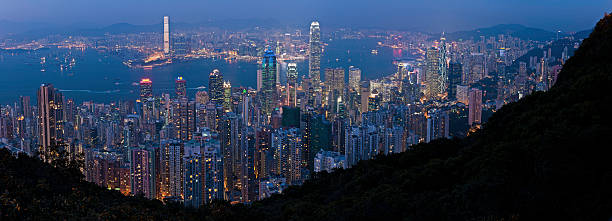 Hong Kong skyscrapers glittering lights downtown harbor night panorama China Sweeping panoramic vista across the crowded city blocks, towering skyscrapers and twinkling lights of high rise apartment blocks overlooking Hong Kong harbor towards Kowloon from Victoria Peak, China. ProPhoto RGB profile for maximum color fidelity and gamut. new territories stock pictures, royalty-free photos & images