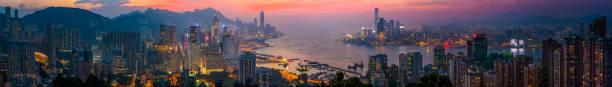 hong kong sonnenuntergang wolkenkratzer panorama über victoria harbour kowloon china - kowloon stock-fotos und bilder