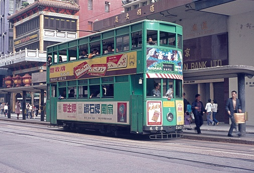 Hong Kong, China, 1974. The unique Hong Kong tram at a stop. Also: passengers, passers-by and buildings.