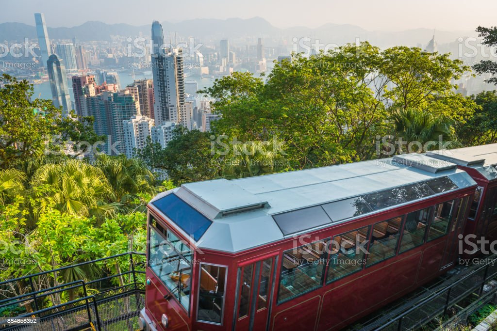 Hong Kong Victoria Peak Tram climbing above harbour skyscrapers China The iconic ruby cable cars of the Peak Tram climbing through the green hillside of Victoria Peak above the crowded skyscraper cityscape of Hong Kong, China. Asia Stock Photo