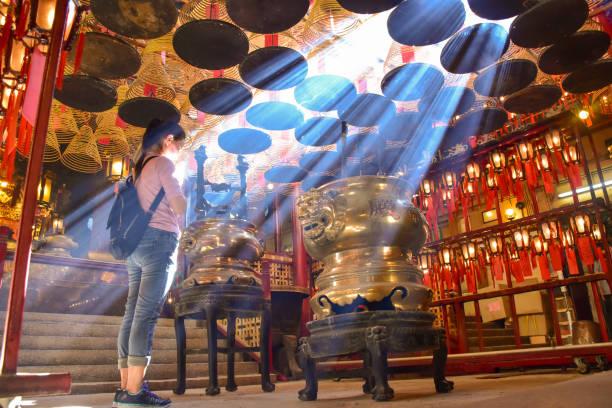Hong Kong-June 10, 2017: asian women prays at Man Mo Temple in Hong Kong with lamps and incense coils hang on the ceiling, free access for everyone Hong Kong-June 10, 2017: asian women prays at Man Mo Temple in Hong Kong with lamps and incense coils hang on the ceiling, free access for everyone taoism stock pictures, royalty-free photos & images