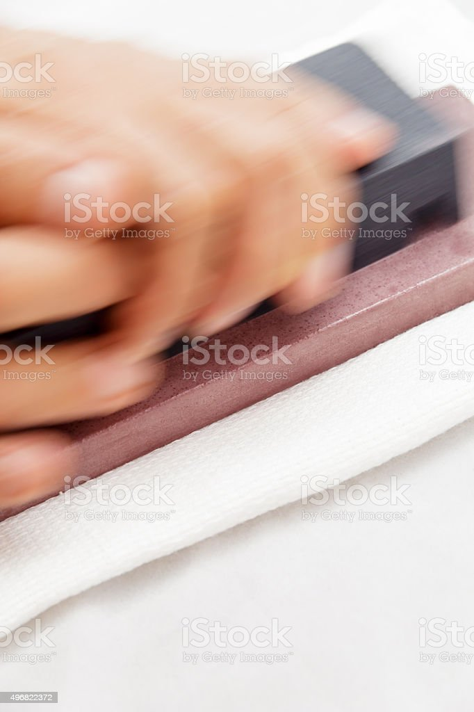 Honing Chef Knife/Close up of hand working Japanese chef knife stock photo