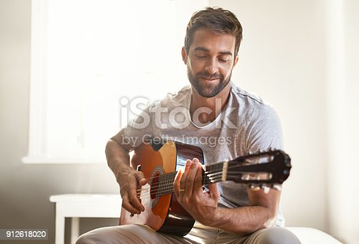 Shot of a handsome young man playing a guitar at home