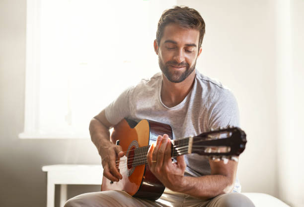 Honing his musical talent Shot of a handsome young man playing a guitar at home guitarist stock pictures, royalty-free photos & images