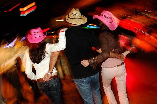 Honky Tonk Country Dancing Threesome A guy and two cowgirls dance in a country western honky tonk bar with neon lights blurred in the background. Shot with slow shutter speed to accentuate motion and action in the scene. country and western music stock pictures, royalty-free photos & images