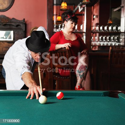 Dapper man in a fedora hat is lining up a billiards shot in a honky tonk saloon while his tattooed retro red dress girlfriend waits at the bar in the background.