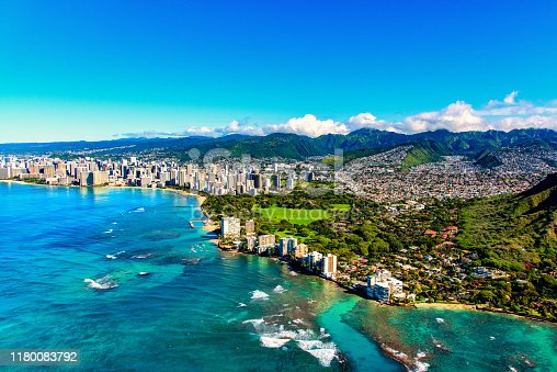 The entire coastline of Honolulu, Hawaii including the base of Diamond Head crater and state park, past the hotel lined Waikiki Beach towards downtown in the distance including the suburban neighborhoods dotting the hills surrounding the city center.