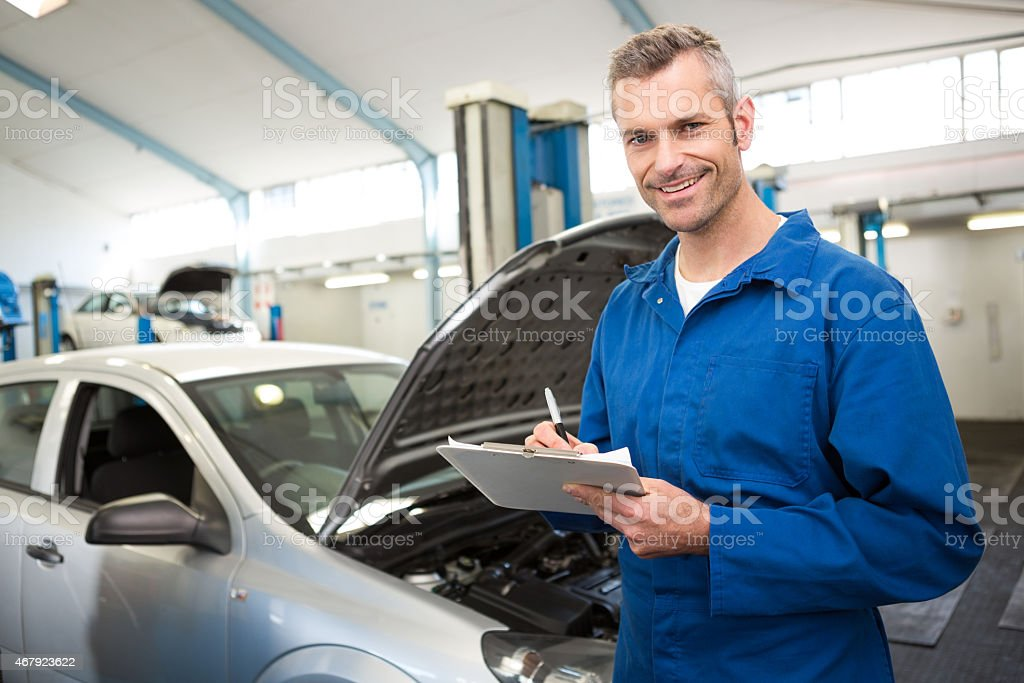 Hood open on a car as a mechanic takes notes stock photo