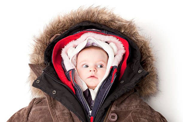 Hooded baby. Little girl in many winter jackets. Concept portrait of a cute 3 month baby girl in many winter jackets. warm clothing stock pictures, royalty-free photos & images