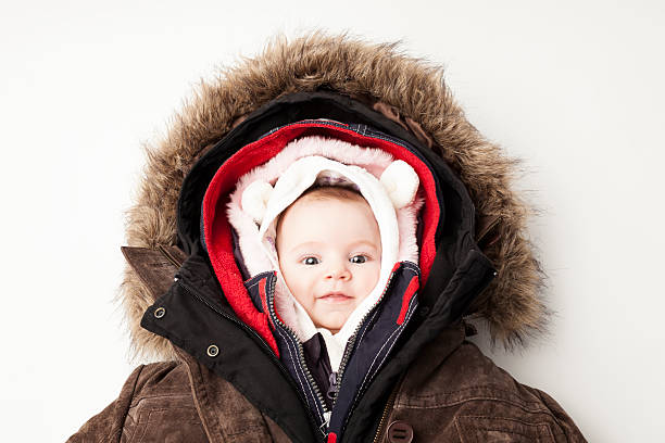 Hooded baby. Little girl in many winter jackets. Concept Shot of a cute 3 month baby girl in many winter jackets. warm clothing stock pictures, royalty-free photos & images