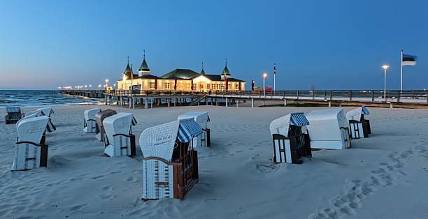 mit kapuze strand stühlen und seebrücke am sand coast - usedom stock-fotos und bilder