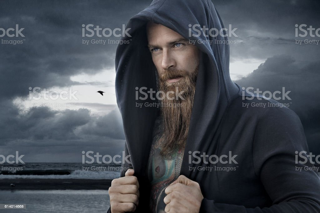 Hooded bearded tattooed male in fantasy cloudy seascape setting stock photo