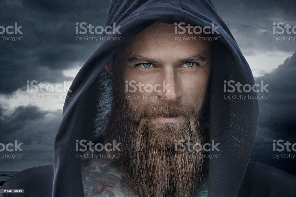 Hooded bearded tattooed male in fantasy cloudy seascape setting - Photo