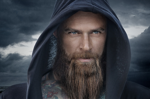 Hooded bearded tattooed male in fantasy cloudy seascape setting stock photo