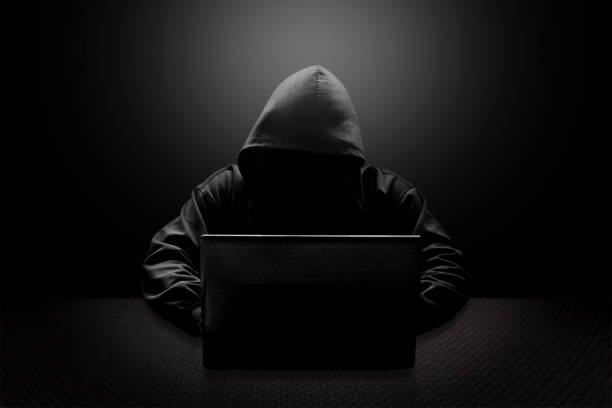 hooded computer hacker stealing information with laptop - hacker stock photos and pictures
