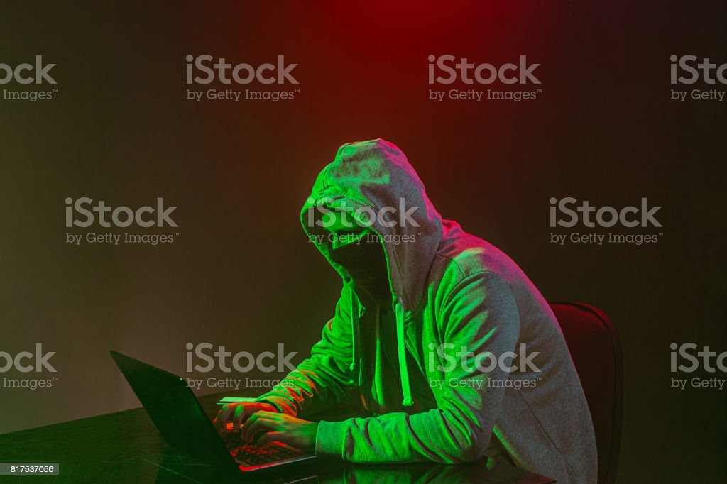 Hooded computer hacker stealing information with laptop stock photo