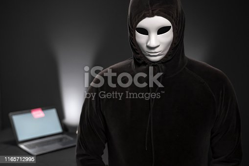 Hooded computer hacker with mask looking at the camera in front of a desk with laptop. The scene is situated in a studio environment in front of a black  background. The picture is taken with Sony A7 III camera.