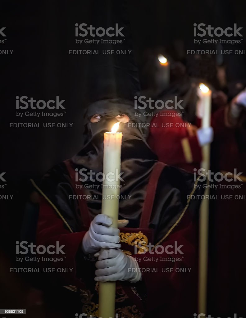 Hooded devotee carries a candle during Holy Week procession in Malaga, Spain. stock photo