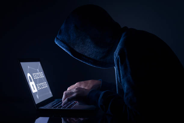Hooded hacker doing cyber attack to secure access, computer screen Hooded hacker in dark room performing a cyber attack to a secure access to steal data on internet, laptop computer screen military attack stock pictures, royalty-free photos & images