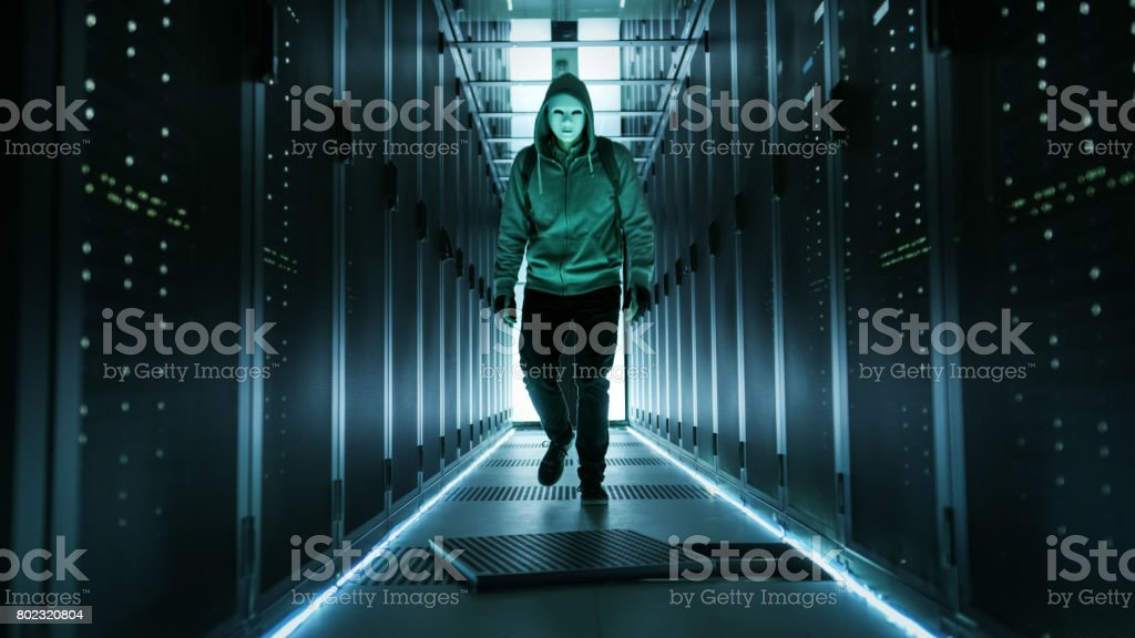 Hooded Hacker in a Mask Walks Through Working Data Center with Open Floor Hatch in the Middle of it. stock photo
