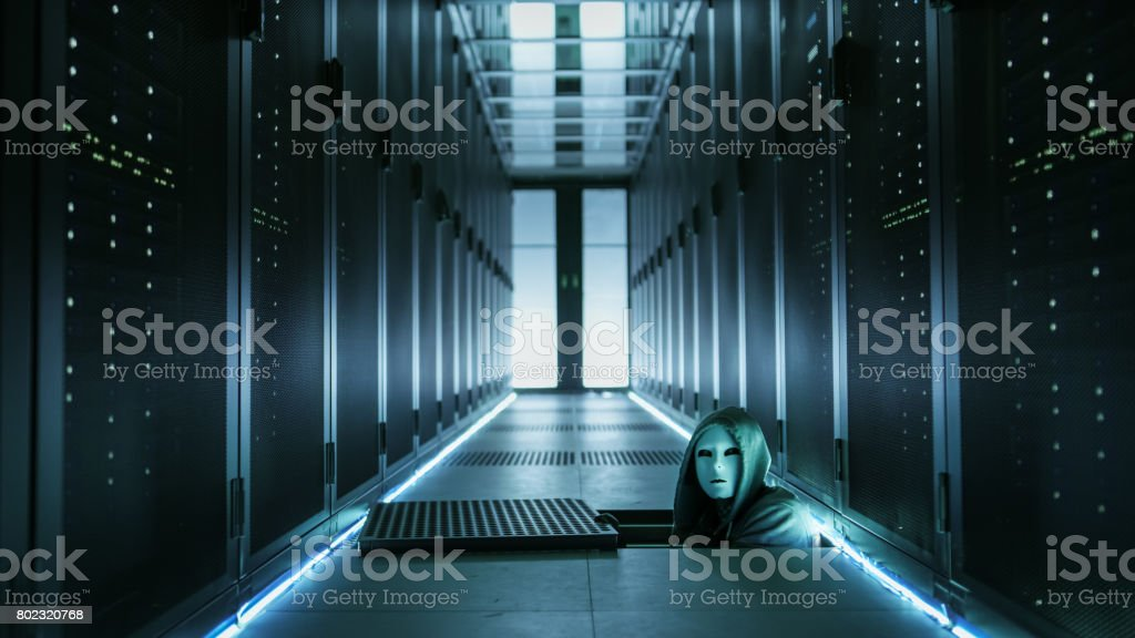 Hooded Hacker in a Mask Watching From Under Floor Hatch in Data Center with Rows of Rack Servers. stock photo