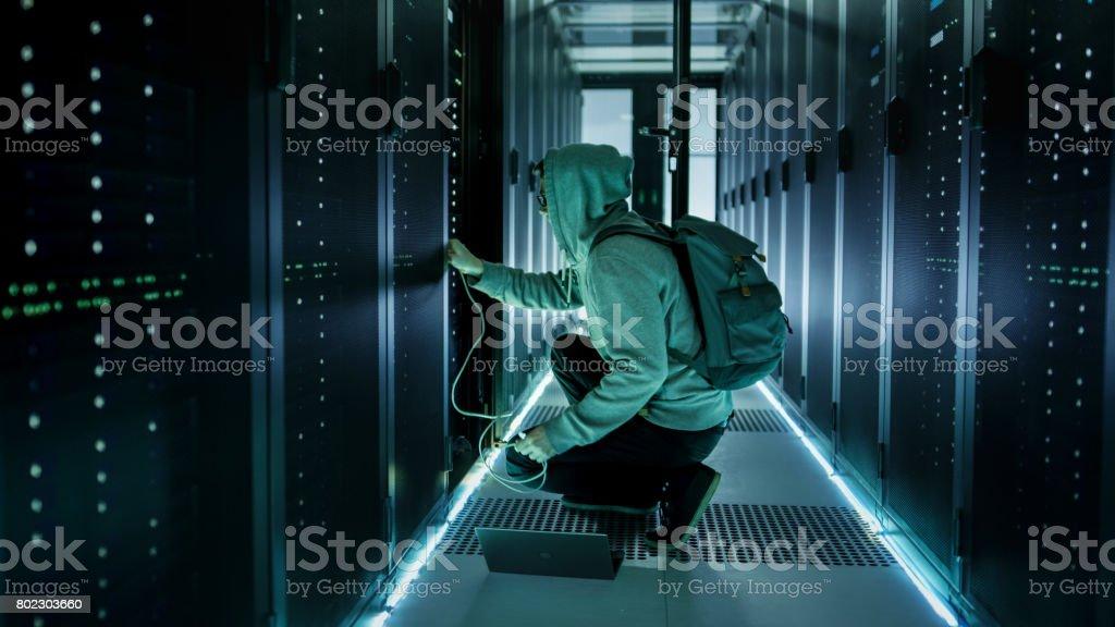 Un Hacker à capuchon avec ordinateur portable se connecte au serveur en Rack et interceptions informations de Corporate Data Center. - Photo
