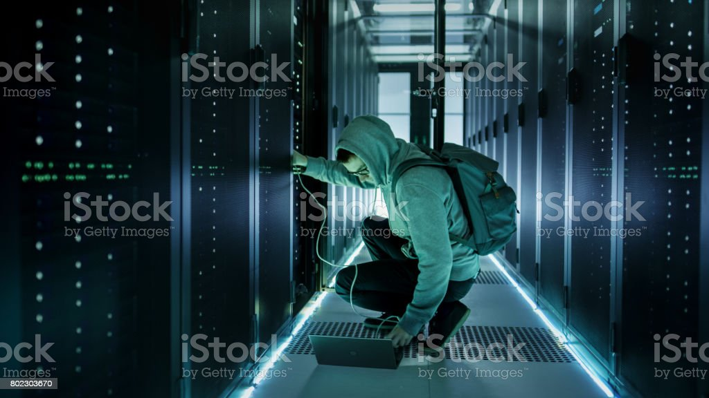 A Hooded Hacker With Laptop Connects to Rack Server and Steals Information from Corporate Data Center. stock photo